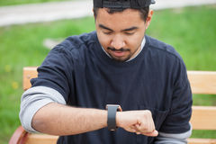 Smiling young black man using smart wrist watches. Young black man using his trendy smart watch sitting in a park on bench .Modern gadget that lets you always Royalty Free Stock Photo