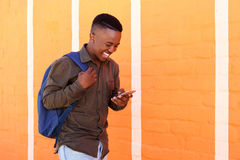 Smiling young black man walking with bag and cell phone. Portrait of smiling young black man walking with bag and cell phone Stock Photo