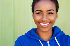 Smiling young black woman against green background Stock Images
