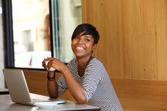 Smiling young black woman with coffee and laptop at cafe Royalty Free Stock Images