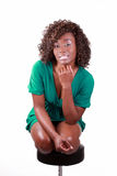 Smiling young black woman kneeling on stool Stock Photos