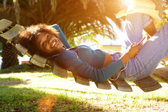 Smiling young black woman listening to music with smart phone Royalty Free Stock Photography