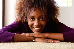 Smiling young black woman lying down on floor Royalty Free Stock Photos
