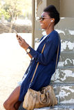 Smiling young black woman outdoors using cell phone. Side portrait of smiling young black woman outdoors using cell phone Royalty Free Stock Image