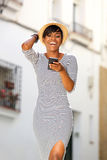Smiling young black woman reading text message on cell phone. Portrait of a smiling young black woman reading text message on cell phone Royalty Free Stock Photos