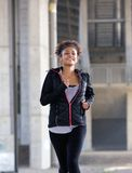 Smiling young black woman running outdoors Royalty Free Stock Photography