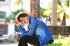 Smiling young black woman sitting in park Stock Photography
