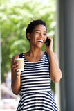 Smiling young black woman in striped dress talking on mobile phone Stock Photo