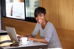 Smiling young black woman using laptop Royalty Free Stock Image