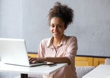 Smiling young black woman working on laptop stock photos