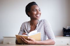 Smiling young black woman writing in journal at home royalty free stock photos