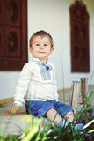 Smiling young blond boy sitting Stock Images
