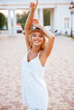 Smiling young blond girl posing with her hands up outside Stock Photos