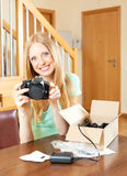 Smiling young blond at the table with new digital camera Stock Photo