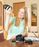 Smiling young  blond unpacking new digital camera and objectives Royalty Free Stock Images