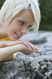 Smiling young blond woman lying on a rock Royalty Free Stock Image