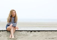 Smiling young blond woman sitting at the beach Royalty Free Stock Photography