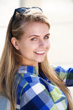 Smiling young blond woman sitting outside Stock Photography
