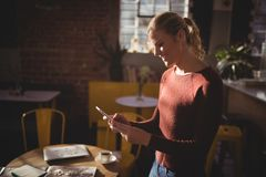 Smiling young blond woman using smartphone at coffee shop Royalty Free Stock Photos