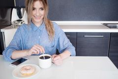 Smiling young blonde eat Breakfast at home. Coffee with donut. Royalty Free Stock Image
