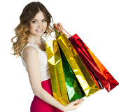 Smiling young blonde girl with colorful shopping bags in white d Royalty Free Stock Photos