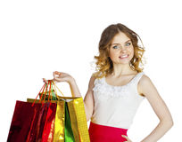 Smiling young blonde girl with colorful shopping bags in white d Stock Image
