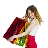 Smiling young blonde girl with colorful shopping bags in white d Stock Images