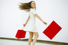 Smiling young blonde girl with colorful shopping bags in white d Royalty Free Stock Photography