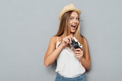 Smiling young blonde girl in hat holding photo camera Royalty Free Stock Photo