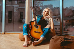 Smiling young blonde lady with guitar in her hands looking at ca. Mera. Girl with guitar. Woman playing guitar. leisure with guitar Royalty Free Stock Photo