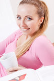 Smiling young blonde woman drinking coffee Stock Image