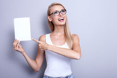 Smiling young blonde woman with empty card. Stock Image