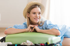 Smiling young blonde woman in hat packing suitcase and looking away Royalty Free Stock Photo
