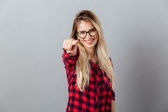 Smiling young blonde woman pointing to you. Royalty Free Stock Photo