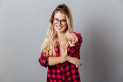 Smiling young blonde woman pointing to you Stock Image