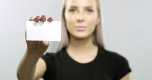 Smiling young blonde woman shows business card stock video