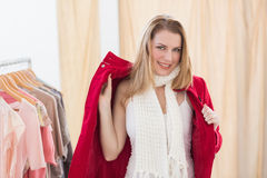 Smiling young blonde woman trying a jacket стоковые изображения rf