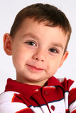 Smiling young boy. A happy, smiling little boy with bright brown eyes and a red and white shirt stock photography