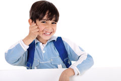 Smiling young boy acts as he talks over phone Stock Image
