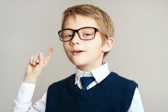 Smiling young boy in big glasses showing finger up over gray background Stock Image