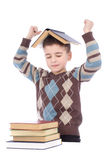 Smiling young boy with a book on his head stock images