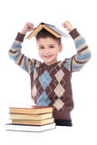 Smiling young boy with a book on his head royalty free stock photos