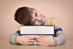 Smiling young boy and books. Smiling young boy sitting at the table and laying his head on the books Royalty Free Stock Image
