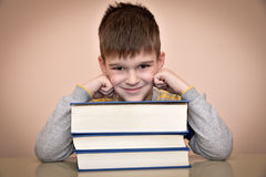 Smiling young boy and books. Smiling young boy sitting at the table and leaning his head on the books Royalty Free Stock Images