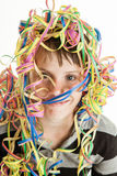 Smiling young boy celebrating his birthday. Or a festive holiday or carnival with his head covered in colorful coiled party streamers over white Stock Photo