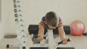 Smiling Young boy doing heavy dumbbell exercise for biceps stock video footage