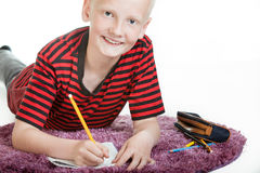 Smiling young boy doing his homework. Lying on a furry purple rug on the floor looking up and grinning at the camera, isolated on white with copy space Royalty Free Stock Image