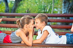 Smiling young boy and girl lying on a park bench. Royalty Free Stock Images