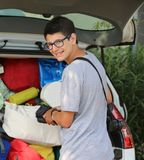 Smiling young boy with glasses puts suitcases in the luggage Stock Image