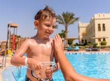 Smiling young boy having sunscreen applied Stock Images